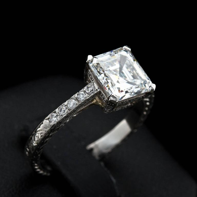 A vintage diamond in platinum engagement ring set with a center 2.52 ct. E color VVS2 clarity (GIA certified) square emerald or Asscher cut diamond and ten round diamond side stones weighing approx. 0.30 ctw.  The ring is a four-prong basket style