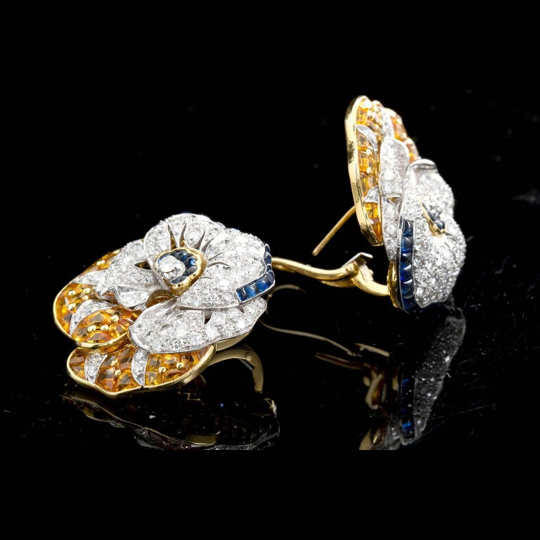 A pair of the famous pansy style earrings by Oscar Heyman. Set with round brilliant cut diamonds, sugarloaf style calibrated blue sapphires and calibrated step-cut faceted yellow sapphires in a hand crafted and stylized 18 karat yellow and white