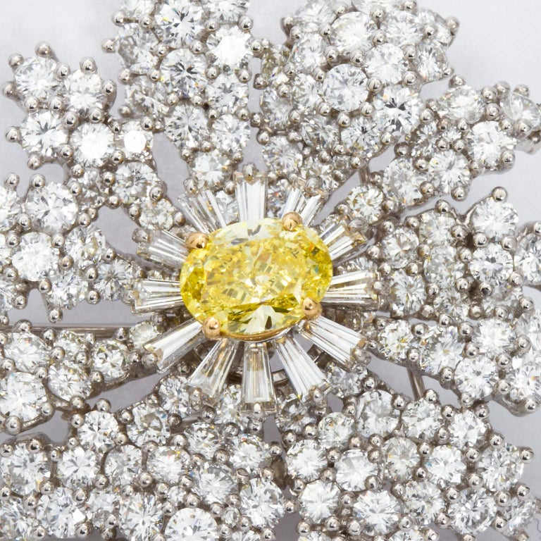 Brooch the subject! A very impressive diamond in platinum flower brooch set with over 20 carats of high quality diamonds and graced with a center approx. 2.00 carats fancy intense yellow oval cut diamond.  Brooch contains round brilliant, calibrated