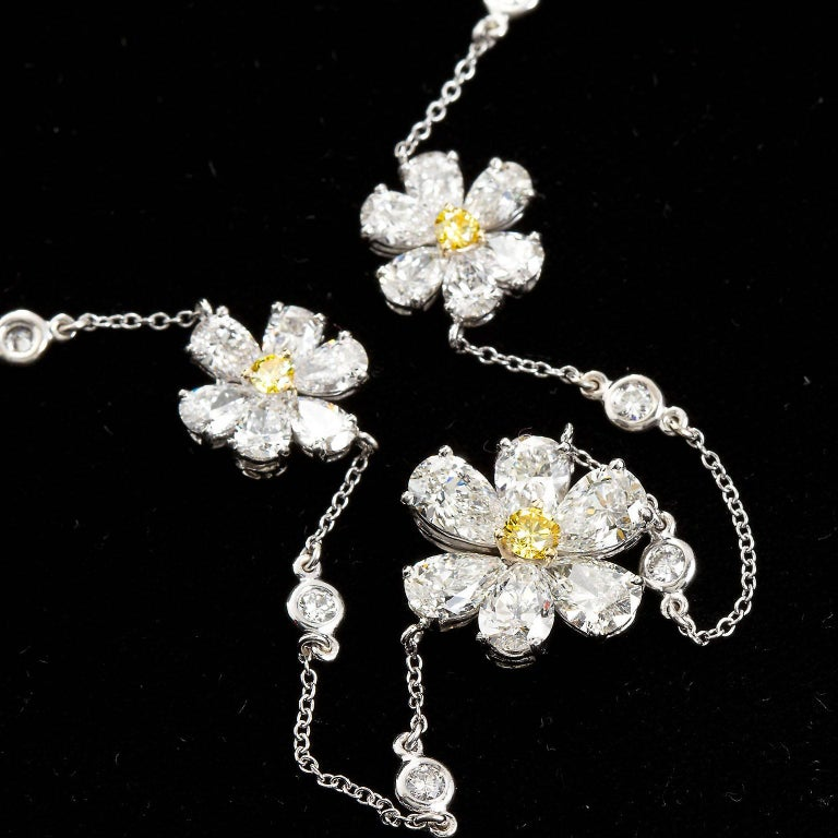 A wonderful diamond pendant necklace with an 18 inch diamond in white gold chain. Center floret contains approx. 3.00 ctw of pear shape diamonds with a center fancy intense yellow round diamond of 0.15 cts. The two smaller florets are each approx.
