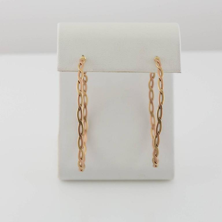 These beautiful woven medium-large sized hoop earrings blend together rose gold twisted with yellow gold accents The hoops are flexible and lightweight and have a matte finish. Very wearable, comfortable and add a little extra intricate detail to