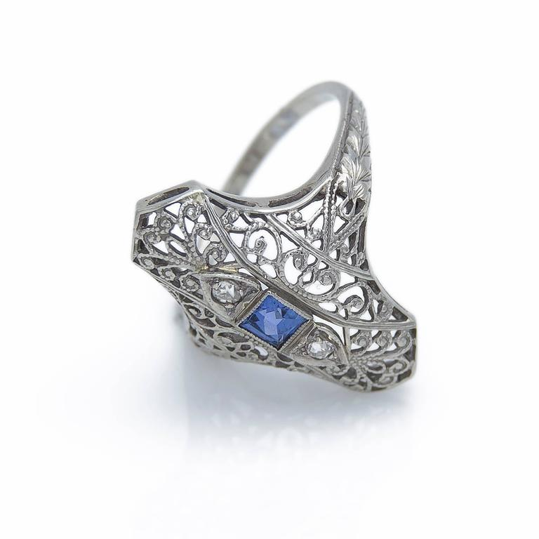 This is a unique and detail oriented piece with intricate filigree work classic of the 1930's Art Deco Era. Adorned with 2 diamonds equaling 0.05 carats and a square blue sapphire in the middle (0.13 carats) this piece exudes brilliance like a