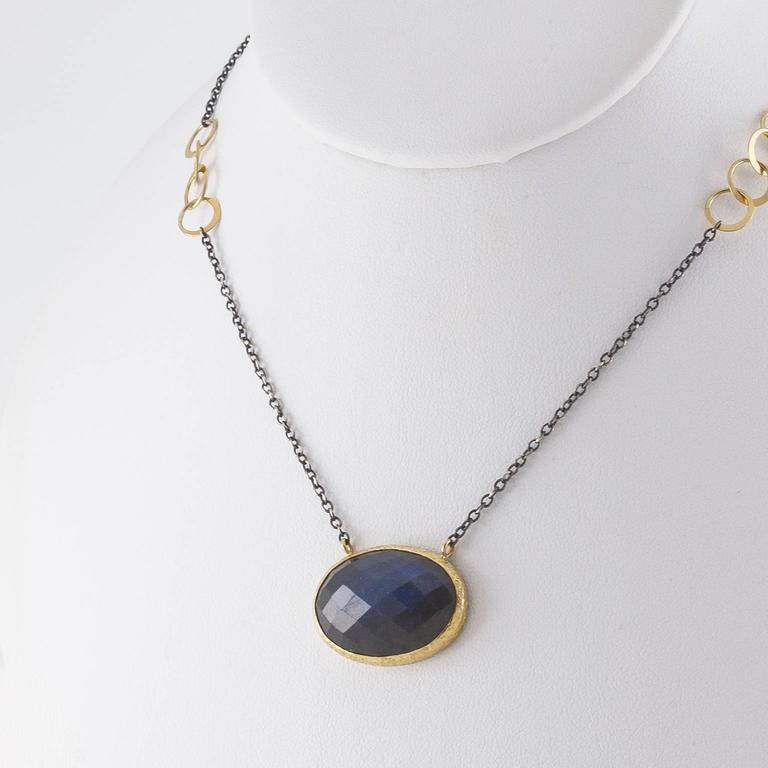 This beautiful and unique piece was hand made in the San Francisco Bay Area.   Unique and exquisite with a two toned chain in yellow gold and oxidized sterling silver this piece is mesmerizing. The gold bezel is hammered and this piece of
