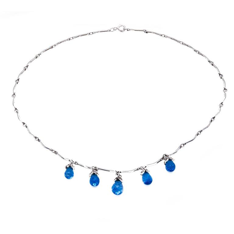 Whimsical droplets of crystal clear blue topaz 'drip' from diamond encrusted buds to create this romantic necklace. Spring is just around the corner and this necklace is just in time to add to your wardrobe!