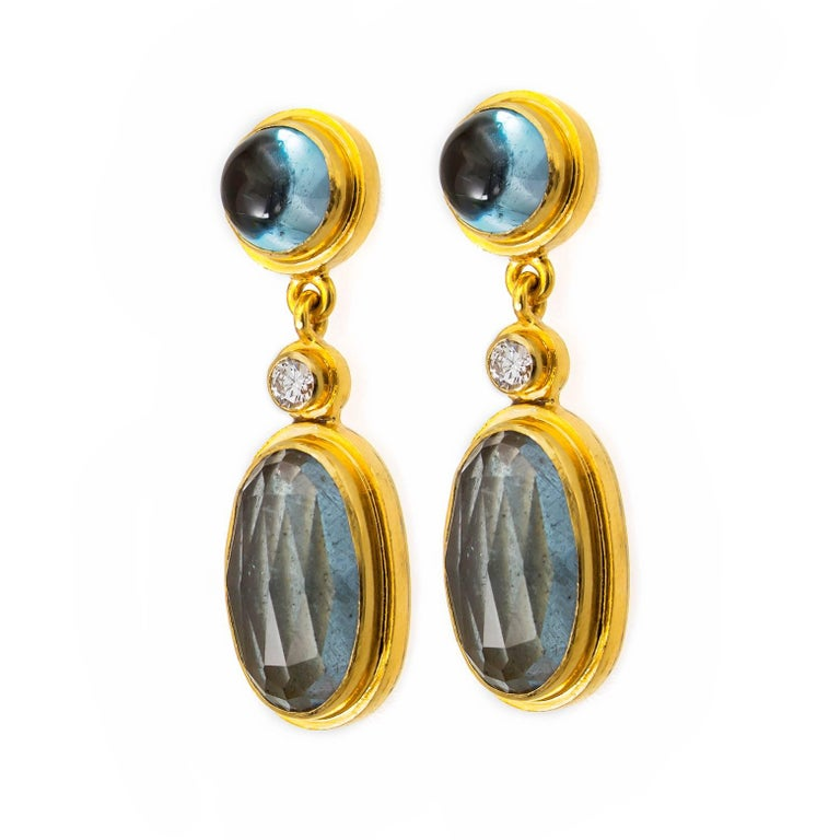 These beautiful, glamorous drop earrings are elegant and earthy set in 18K yellow gold with white diamond accents, blue tourmaline, and oval faceted moss aquamarines. Calming watery earth tones with bright yellow gold compliment these beauties