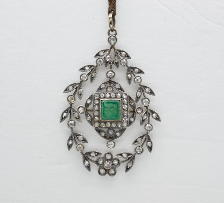 This large wreath-like pendant is full of old mine cut diamonds and a hinge in the middle to create a swinging movement.  A large bright green emerald glows in the center with horizontal inclusions and historical allure. It is on a braided cord so