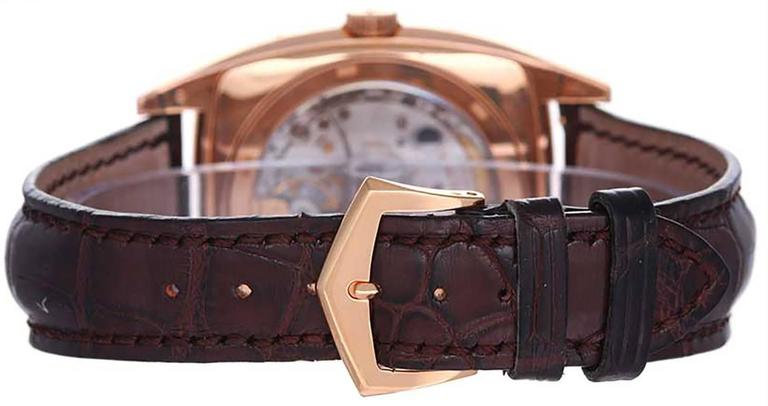 Automatic winding; annual calendar. 18k rose gold case with exposition back to view movement (39mm x 51mm). Silvered dial with gold markers and Arabic numerals; day, date, month, moonphase and a.m./p.m. indicator. Strap band with 18k rose gold Patek