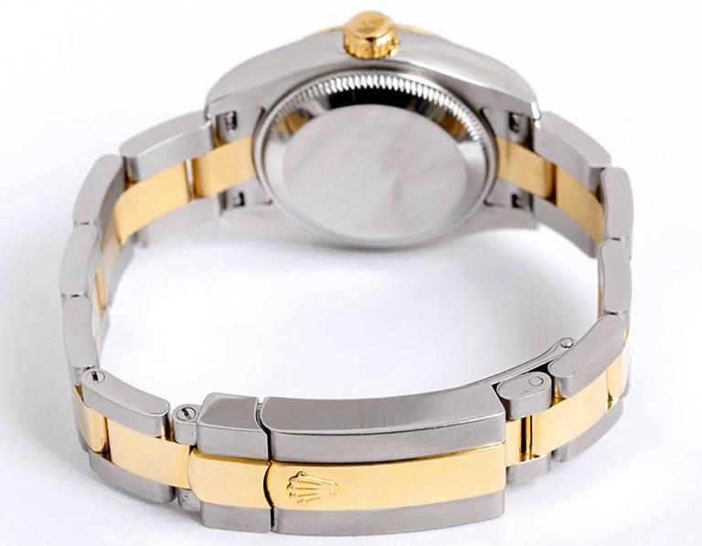 Automatic winding, Quickset, 31 jewels, sapphire crystal. Stainless steel case with 18k yellow gold fluted bezel (26mm diameter). Champagne Jubilee dial with factory diamond hour markers. Stainless steel and 18k yellow gold Oyster bracelet.