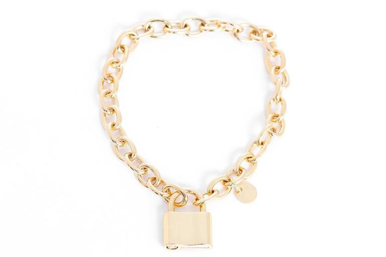 This amazing Tiffany & Co. chain link bracelet features a padlock charm in 18k yellow gold. Bracelet measures apx. 7-inches in length. Padlock charm measures apx. 3/4-inch in length and apx. 9/16-inch in width. Hallmarked,