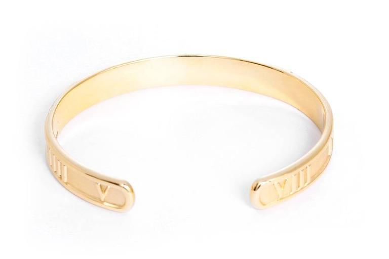 "This Tiffany & Co. Atlas cuff features a roman numeral design in 18k yellow gold. Bracelet measures apx. 5/16-inch in width and fits up to apx. 6-1/2 inch wrist. Total weight is 24.8 grams.  Bracelet is marked, ""Tiffany & Co. 1995 750 Italy""."