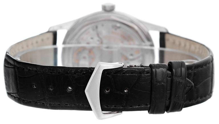 Automatic winding. 18k White gold case with exposition back (37mm diameter). Black dial  with white Arabic numerals; seconds subdial between 4 & 5 o'clock; large hand with red half moon points to date. Strap band with 18k white gold Patek Philippe
