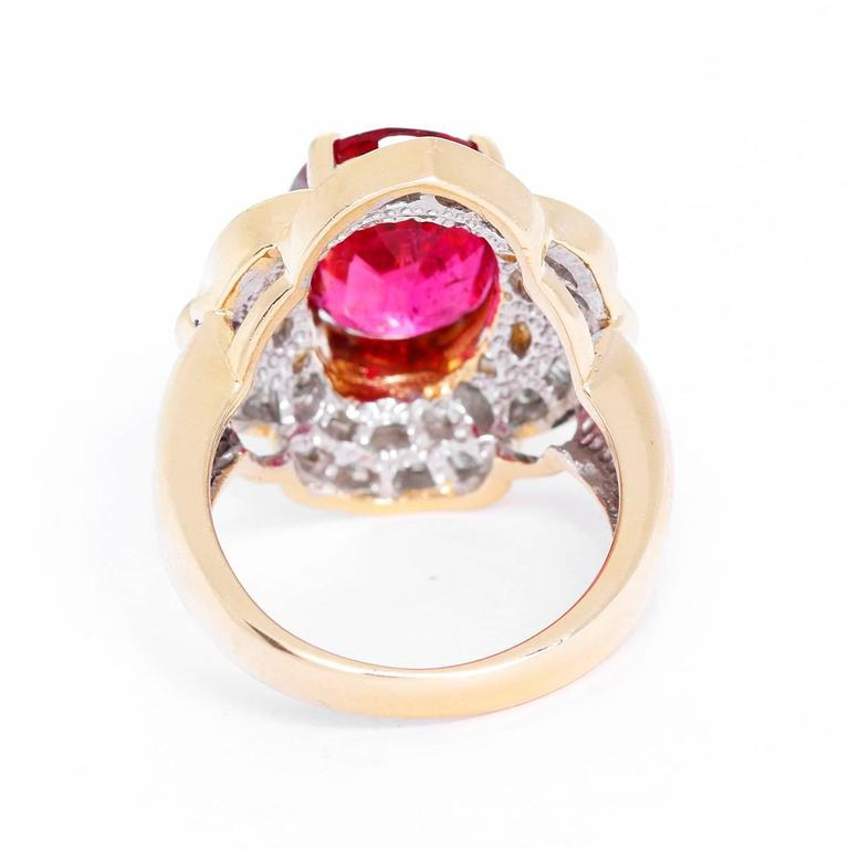 This stunning ring features central oval-cut rubellite tourmaline, with apx. 5.12 cts., surrounded by six round brilliant-cut and sixty-six baguette-cut diamonds, with apx. 0.79 cts. Total weight is 11.0 grams. Size 7.