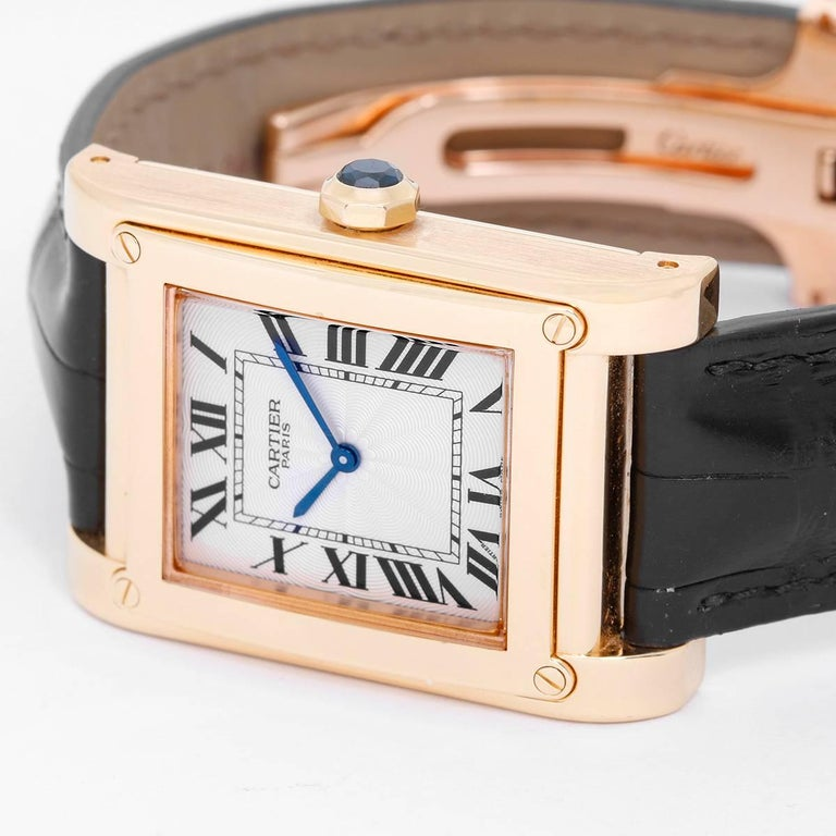 Cartier Tank A Vis Ref 2608 F Watch -  Manual. 18K Yellow Gold ( 18 mm x 40.5 mm ). White dial with Roman Numerals. Cartier black strap with 18K gold Cartier deployant clasp. Pre-owned with box and papers. Service papers, original invoice too. Full