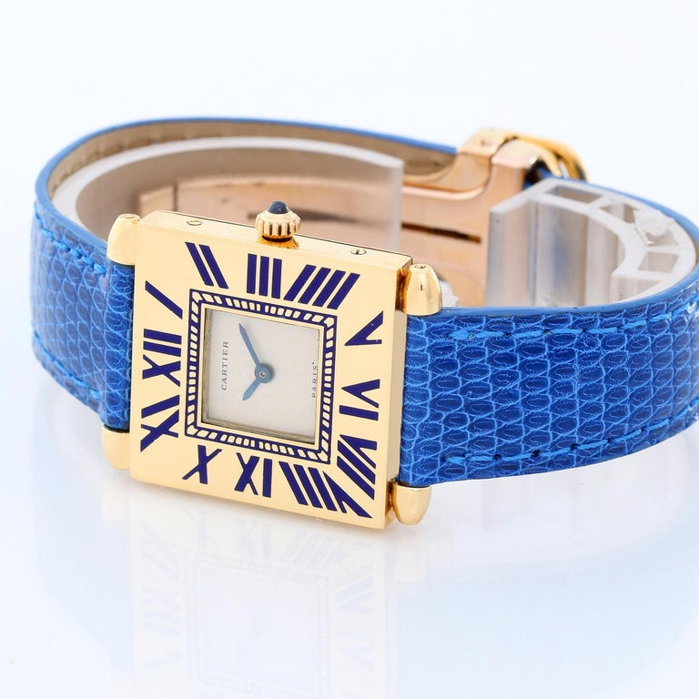Cartier 18k Yellow Gold Quadrant Ladies Watch - Quartz. 18K Yellow gold ( 25 mm x 32 mm ) grained blue Roman numerals. Ivory dial with blue hands. Blue Cartier leather strap. Pre-owned with custom box.