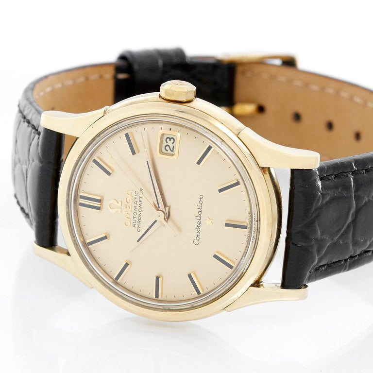 Omega Constellation Automatic 18K Yellow Gold Watch - Automatic . 18K Yellow gold case ( 34 mm ) . Champagne dial with raised stick hour markers . Black leather strap with tang buckle . Pre-owned with custom box .