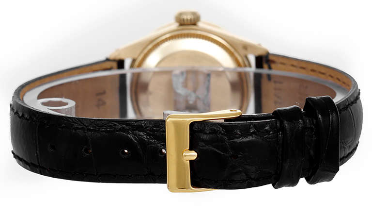 Automatic movement, 28 jewels, acrylic crystal, circa 1970s. 18k yellow gold case, 26mm diameter, with custom diamond bezel. Black dial with gold baton markers. With Rolex box and books.