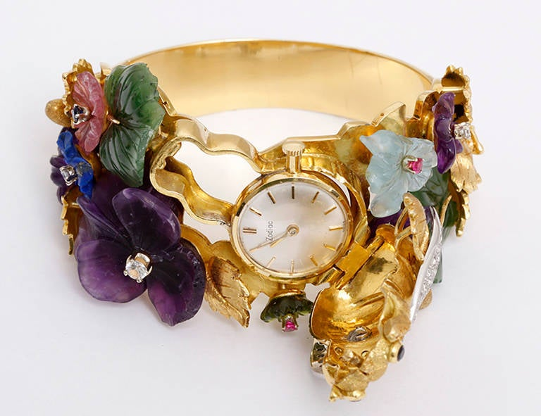 Manual-wind movement signed Zodiac. 18k yellow gold case features a large bee of simulated diamonds concealing the dial of the watch. Carved amethyst, rose quartz, aquamarine, lapis, and nephrite flowers adorn the bracelet. Silvered dial with gold