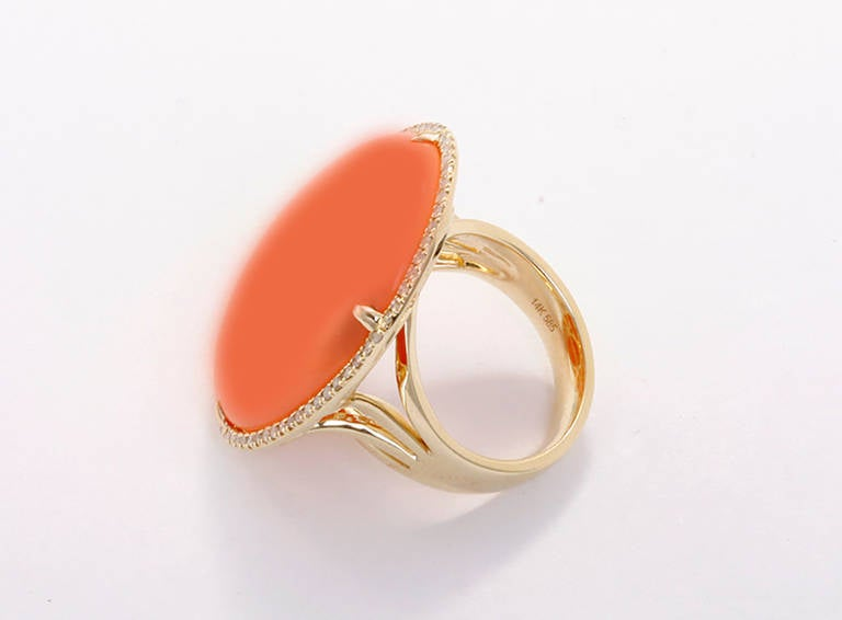 This is a beautiful 14k yellow gold, imperfect oval orange agate cabochon ring measuring apx. 26 mm in width by apx. 32 mm in length.   It features an accenting border of  apx. 0.27 carat diamonds. The ring is a size 7 with a total weight of 14.5