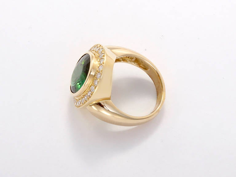This stunning ring features a 5.85 carat green tourmaline centered by accenting diamonds set in 18k yellow gold. It measures apx. 20 mm in length and 17 mm in width. The ring is a size 5-3/4 and is sizeable. Total weight is 11.6 grams.
