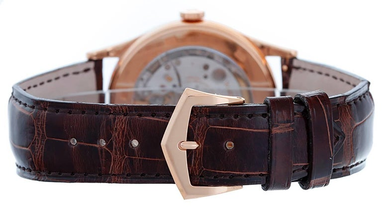 Automatic winding. 18k rose gold case with exposition back to view movement (38mm diameter). Silvered dial with black index markers; date at 3 o'clock position. Patek Philippe strap band and 18k rose gold buckle. Pre-owned with box and papers.