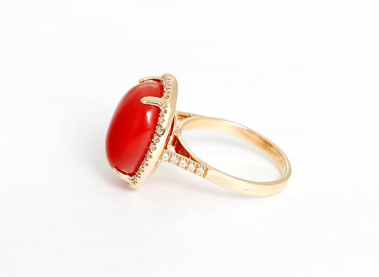 This beautiful ring features an oval-shaped coral cabochon bordered by apx. 0.40 carats of diamonds  in 14k yellow gold. Ring measures apx. 15.3 x 12.7 x 9.0mm.  Total weight is 6.4 grams. Size 6-1/4.
