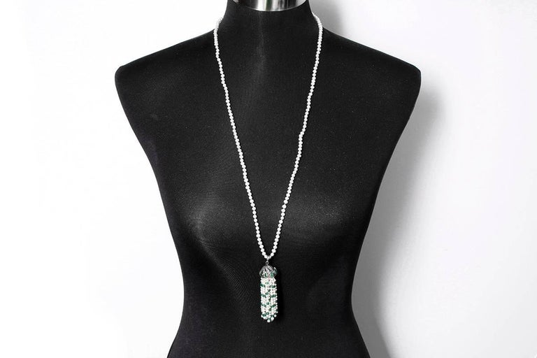 This pearl necklace  features a tassel with emeralds, pearls, and 1.06 carats of diamonds set in  silver. The necklace measures apx. 32-inches and the pendant measures apx. 3-inches in length. Total weight is 42.6 grams.