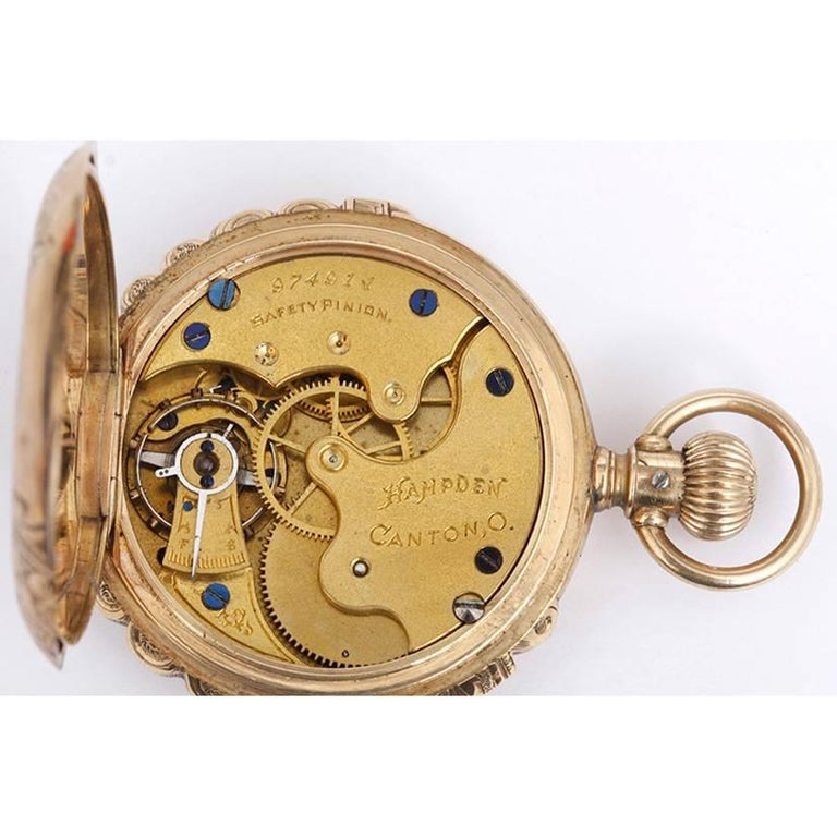 Hampden 14k Yellow Gold Scalloped Case Manual Winding Pocket Watch.  Elaborately engraved yellow gold scalloped case. White enamel dial with black Roman numerals. Pre-owned, ca. early 1900's.