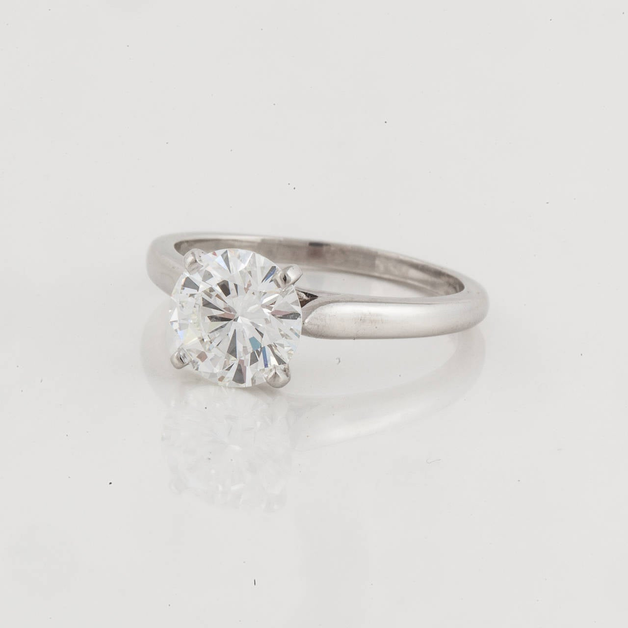 Cartier platinum diamond solitaire ring.  Four prong mounting holds a round brilliant cut diamond weighing 1.67 carats. Color is H and clarity is VS1.  Ring is currently a size 6-1/4 but, of course, can be resized. Engraved on inside of band