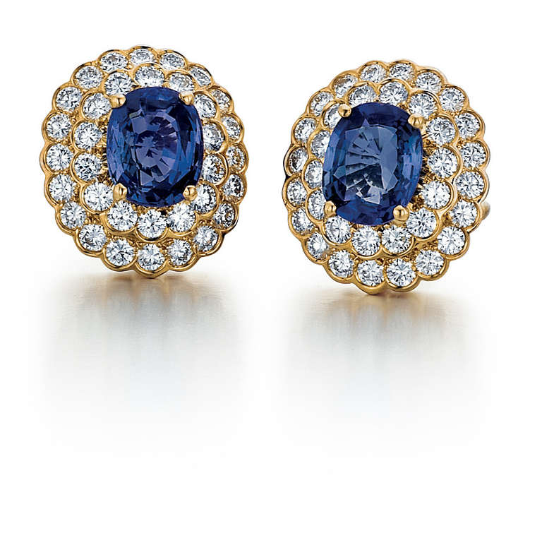 These 18kt yellow gold earrings were made by Oscar Heyman & Brothers. They feature two oval blue sapphires that weigh 6.91 carats total weight. There are also 68 round diamonds that are 3.78 carats total weight.