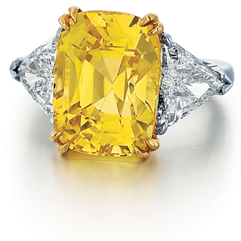 This three stone ring is composed of 18K yellow gold and platinum, and features a yellow sapphire accented by diamonds.  The cushion-cut yellow sapphire is 16.79 carats and is accompanied by a GIA report.  The report states the stone is natural with