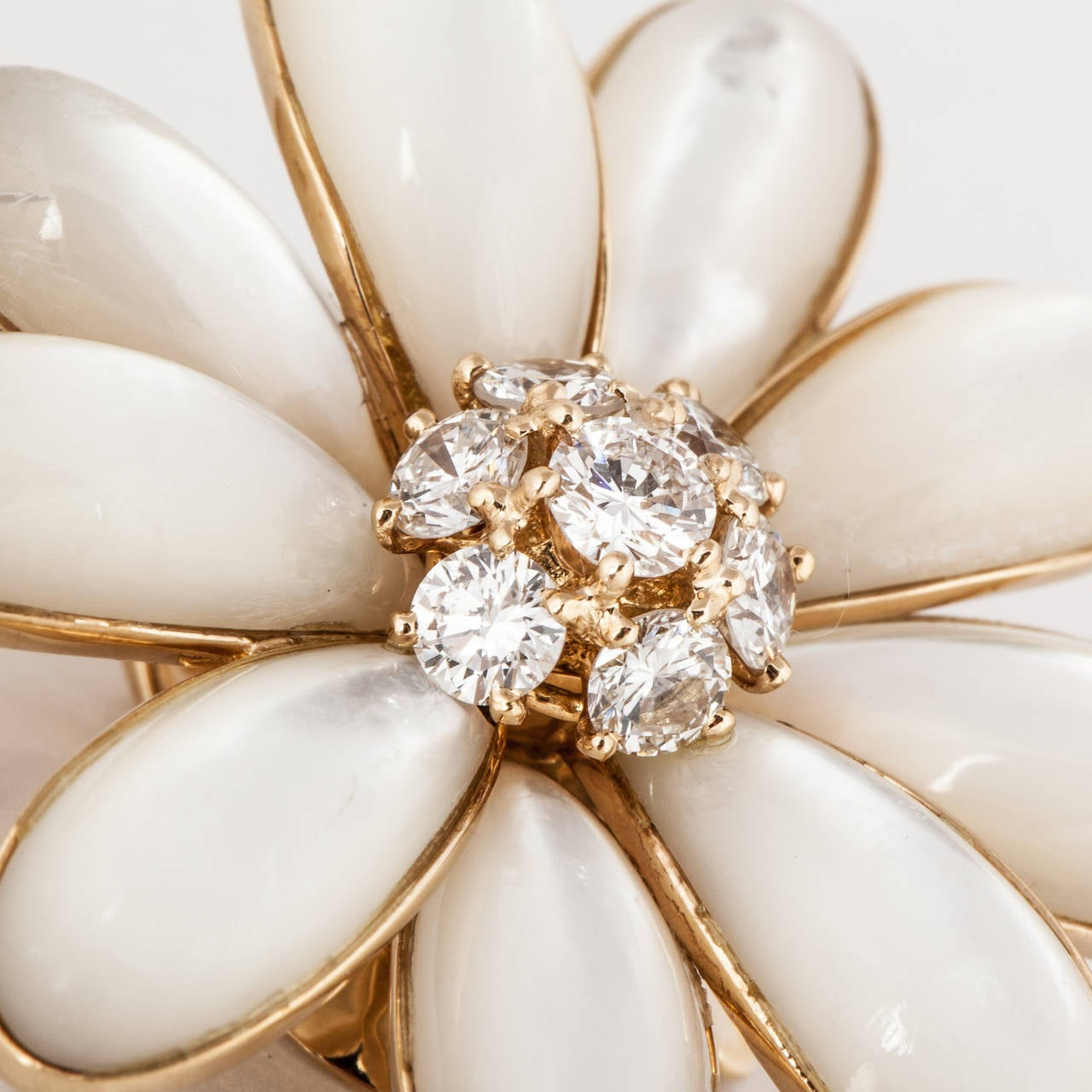 """Yellow gold clip-on earrings made with Mother of Pearl with diamond centers.  Marked """"V.C.A. 750 B3396 P22"""".  There are eighteen (18) mother of pearl petals with fourteen (14) round brilliant cut diamonds totaling 1.50 carats.  They are F-G in color"""
