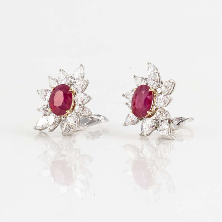These earrings feature two beautiful oval Burmese rubies mounted in 18kt yellow gold. The total weight of the rubies is 9.5 carats, and they are accompanied by GIA Reports. There are also 24 pear-shape diamonds mounted in platinum, weighing 7.2