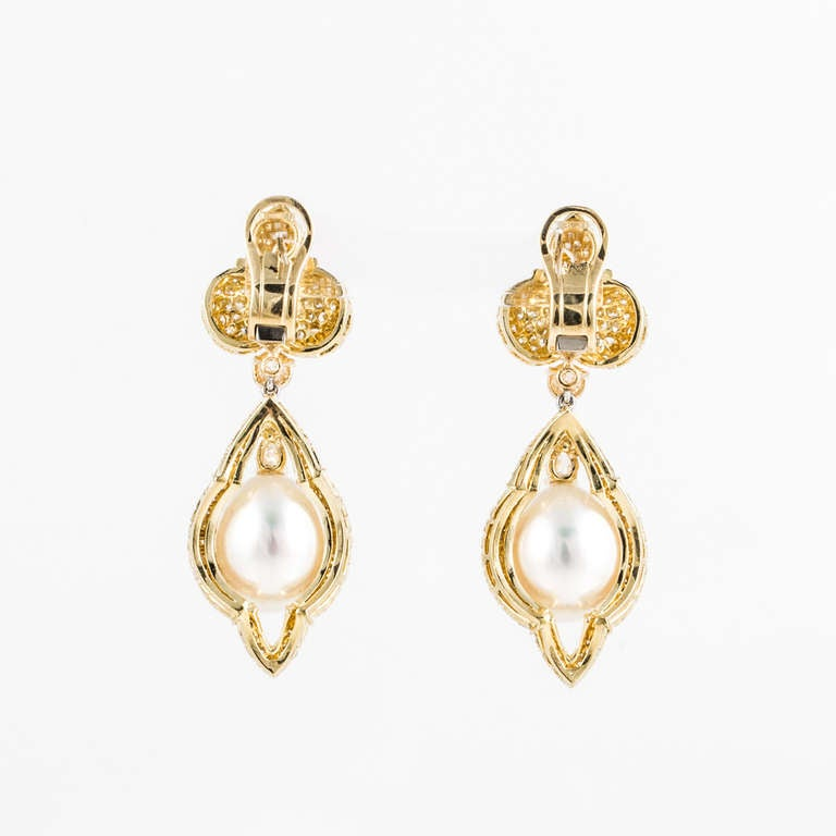 These Henry Dunay earrings are in 18kt yellow gold. They feature two cultured South Seas pearls, each measuring 16mm x 12.5mm. The earrings are also accented by round pave-set diamonds that weigh 7.70 carats total weight and 2 pear-shape diamonds