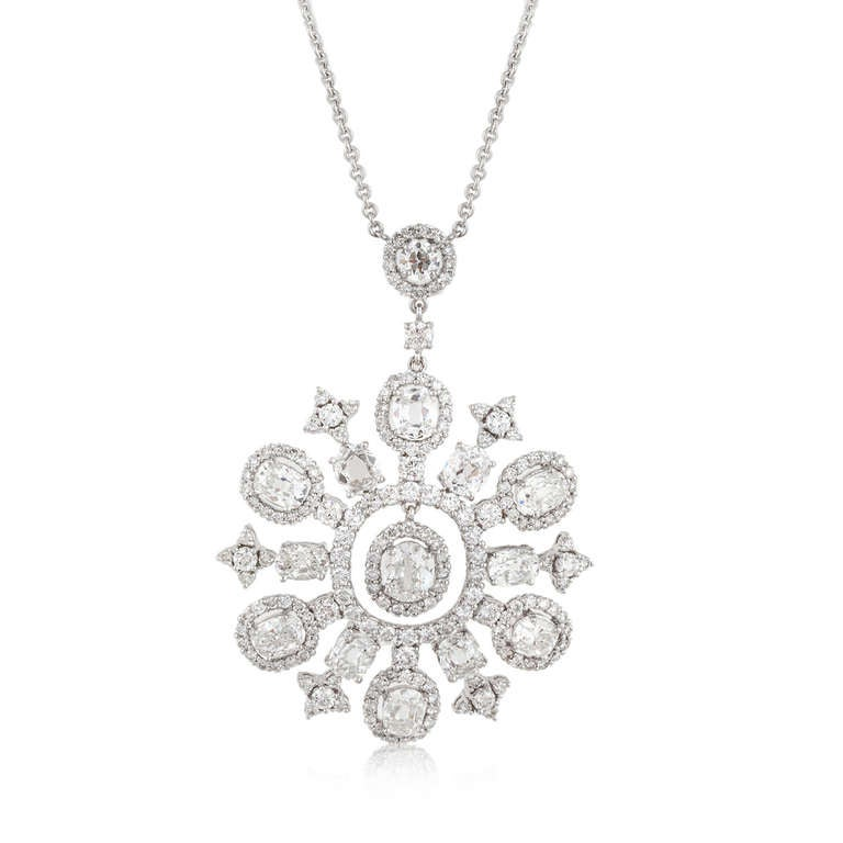 This necklace with a snowflake design is in 18kt white gold. It features a combination of oval and round diamonds that are approximately 9.6 carats total weight. The pendant is affixed to a cable chain that also has diamond accents.