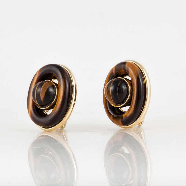 These 18kt yellow gold earrings feature a round cabochon cut tiger's eye quartz in the center as well as an oval tiger's eye ring surrounding it.