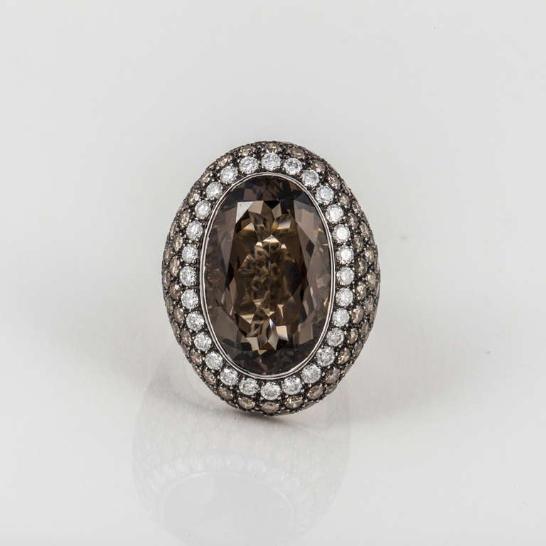 This 18kt white gold ring features a large oval smoky quartz in the center, surrounded by 122 white and brown diamonds weighing 4.90 carats total weight. The ring is currently a size 7.