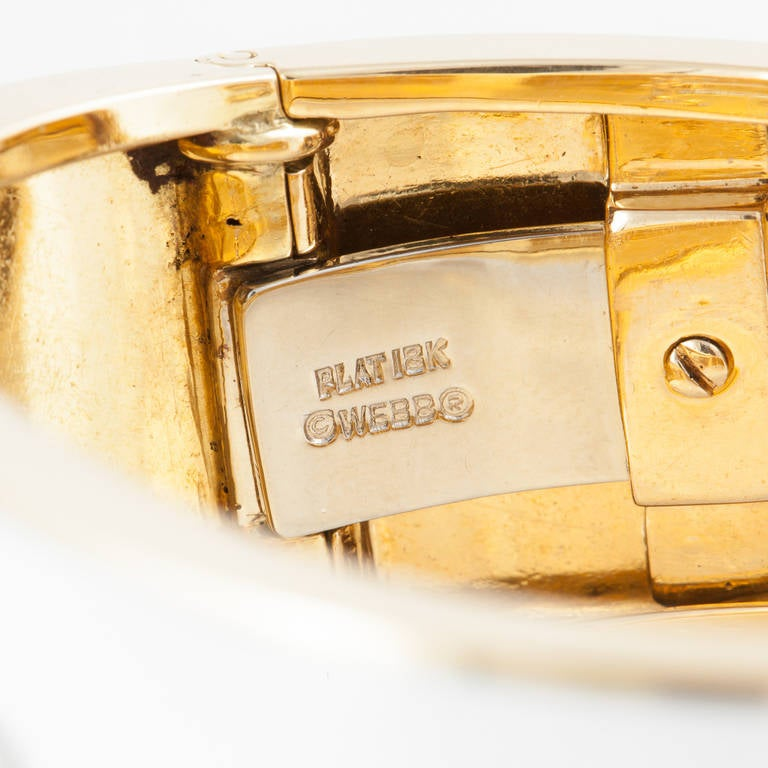 This cuff bracelet by David Webb is entirely covered with white enamel over 18kt yellow gold. It has a graphic design of diamonds on the top, set in platinum. There are 3.40 carats total weight of diamonds.