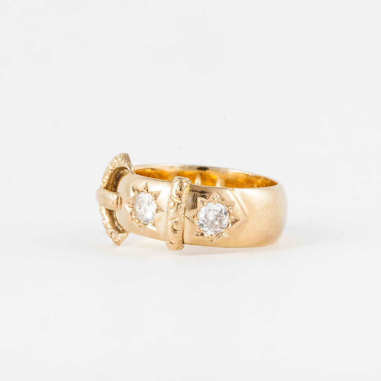 18K yellow gold buckle ring with hallmarks indicating ring was made in London in 1917.  Features two (2) Old Mine cut diamonds with a total weight of 0.75 carats. Beautiful engraving with diamonds set inside a star pattern.  Measures 3/8 of an inch