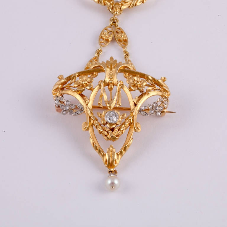 This beautiful art nouveau necklace features a detachable pendant that can also be worn as a brooch. It is in 18kt yellow gold, with platinum accents on the pendant. There at 1.18cttw of diamonds, and one cultured pearl.