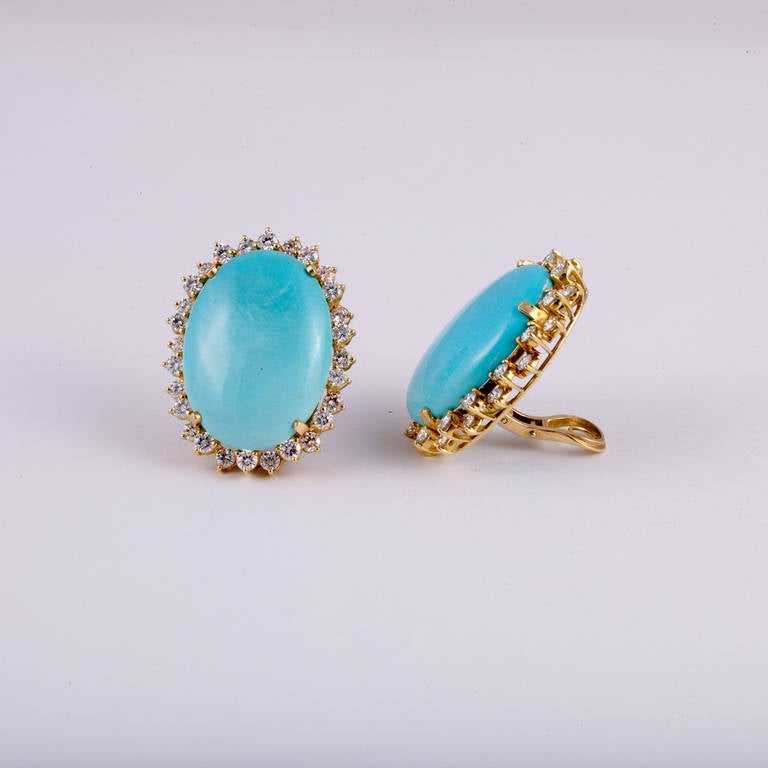 These earrings in 18kt yellow gold features large oval shaped turquoise stones, surrounded by round diamonds with a total carat weight of 5.60ct.