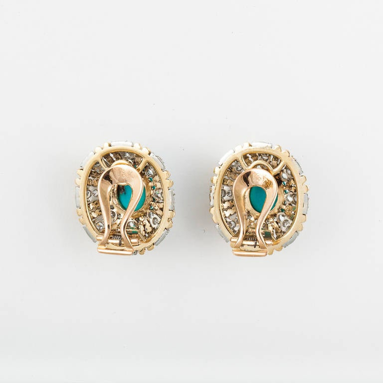 These earrings are in 18kt yellow and white gold. They feature 2 oval cabochon turquoise surrounded by yellow gold and 3.40cttw of diamonds.