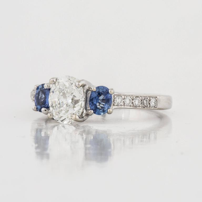 This three-stone ring is composed of 14K white gold with diamonds and sapphires.  The center diamond is 0.94 carats, H-I color and SI1-SI2 clarity.  On each side of the central diamond are two (2) oval sapphires that total 0.40 in carat weight.