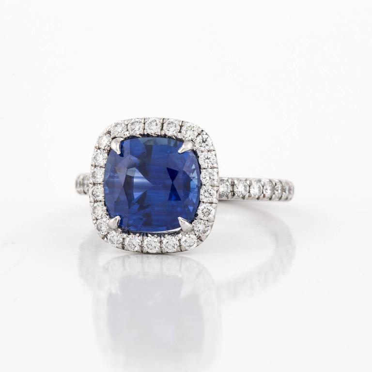 This halo style ring features a cushion cut sapphire with round diamonds, in platinum.  The sapphire totals 3.27 carats.  There are fifty-six (56) round diamonds that total 0.85 carats, G-I color and VS clarity.  Presentation area is 1/2 inch.  Ring