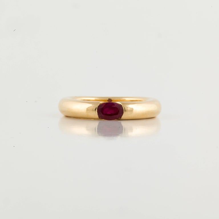 Cartier Ellipse ring in 18K yellow gold featuring an oval faceted ruby. The ring is marked