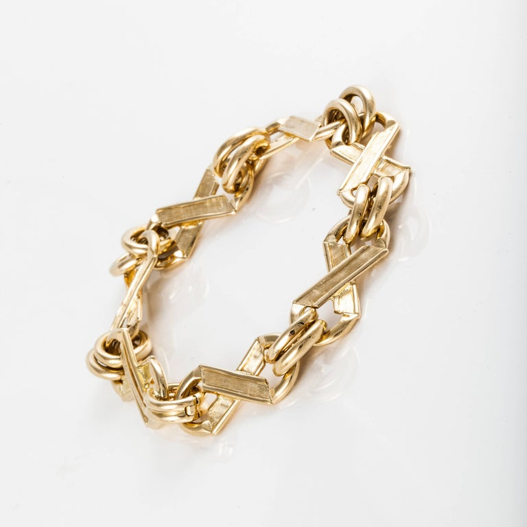 This classic bracelet by Tiffany & Co. Schlumberger is 18K yellow gold.  It depicts  X's and O's with both a brushed and smooth finish.  The bracelet is marked