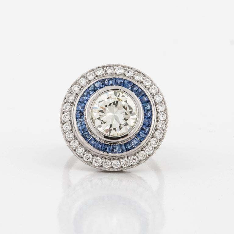This beautiful ring is a contemporary version of the vintage target rings.  It is composed of platinum with diamonds and sapphires.  The center diamond is a round brilliant-cut, 2.75 carats, M color, and VVS2-VSi1 clarity.  There are forty-one (41)