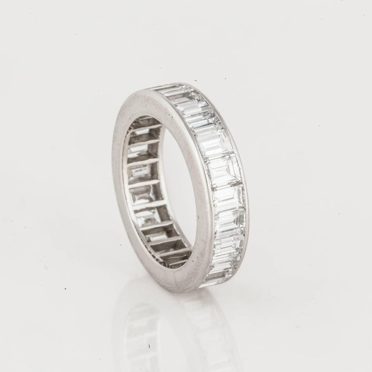 This classic eternity band in platinum features emerald cut diamonds.  There are twenty three (23) emerald cut diamonds totaling 4.60 carats, G-H in color and VVS2-VS1 in clarity.  Ring is a Size 6 and measures 3/16