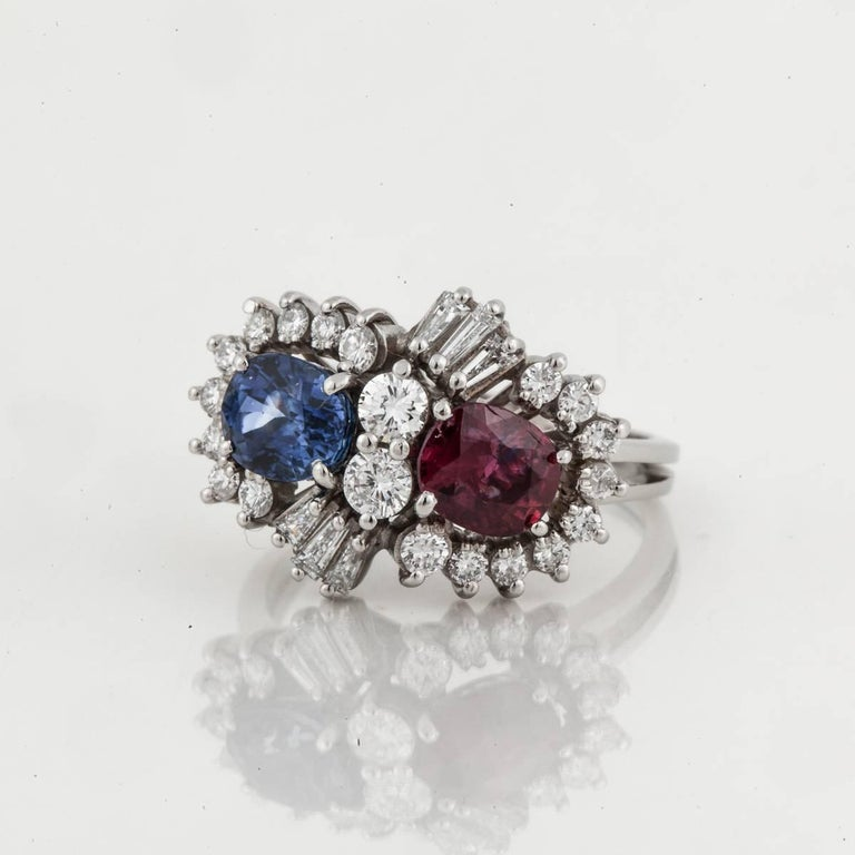 This ring is crafted in platinum and holds a ruby and sapphire surrounded by diamonds.  One oval ruby weighs 1 carat and the oval blue sapphire also weighs 1 carat.  There are 1.15 carats of round and baguette diamonds, H-J in color and SI clarity.