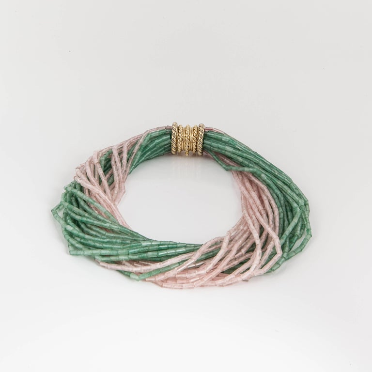 This necklace features strands of green and pink quartz beads forming a twisted necklace.  The yellow gold clasp has a rope design and is inscribed on the inside
