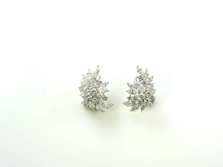 A pair of platinum and diamond crescent leaf cluster form earrings, by Tiffany & Co., Circa 1960.  Signed Tiffany & Co.  The earrings contain a total of 30 round brilliant cut diamonds weighing a total of approximately 4.16 carats, and 18 marquise